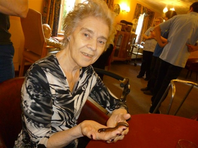 Resident Joan S holding a millipede which had been brought in along by Banham Zoo for a visit along with several other animals
