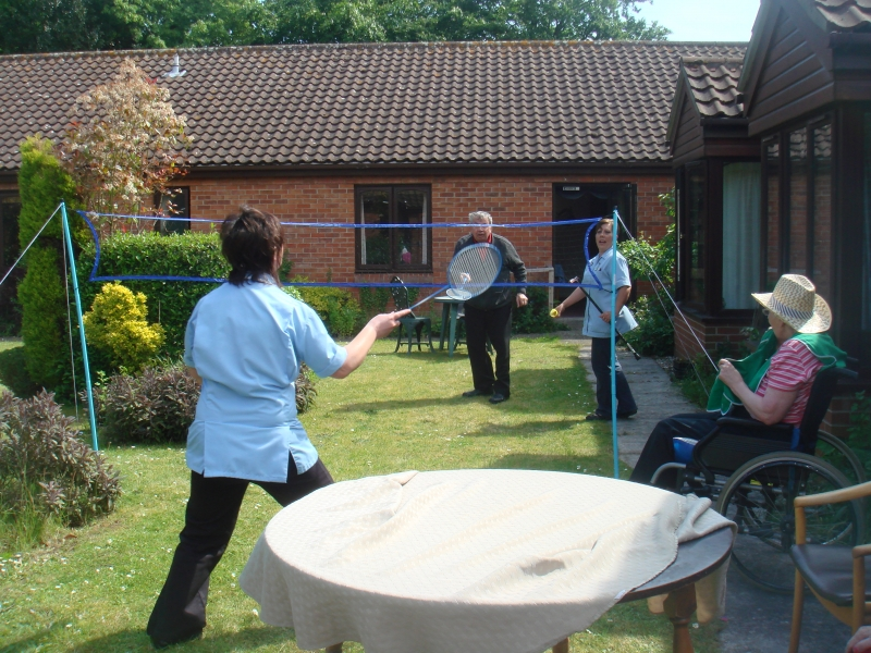 Carer Tarnya and resident James enjoying a game of badminton helped by carer Wendy and resident Ann overseeing the game!