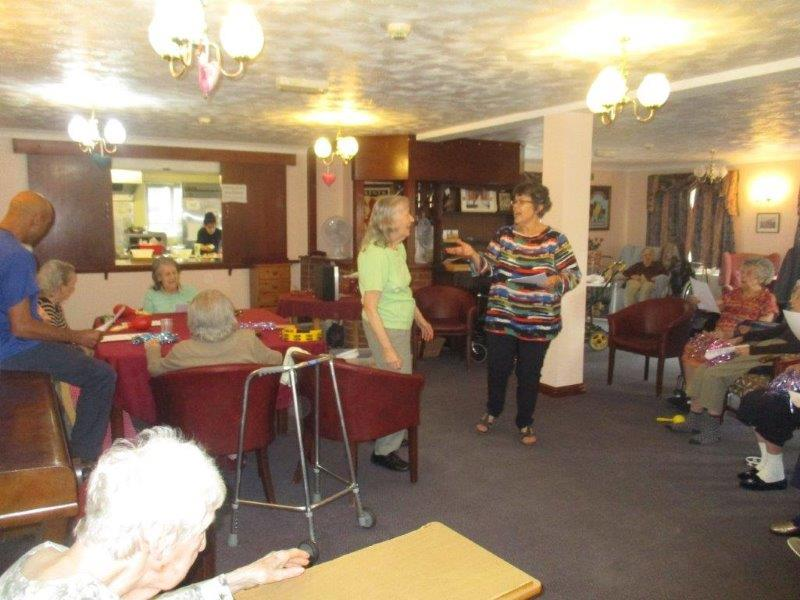 Linda, in her colourful top, stood with resident Jennifer singing to other residents at Dorrington House Watton!