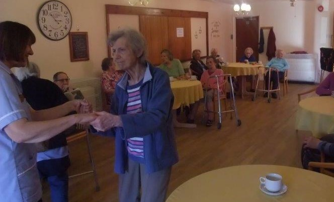 Carer Joy and resident Sally having a dance to the music other residents relax and enjoy their hot drinks at Dorrington House Dereham!