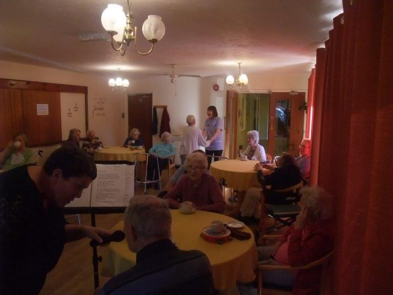 Peter having a sing song while in the background residents listen enjoying a cup of tea. At the same time Resident Ann and Carer Joy have a dance!