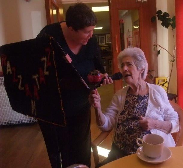 Resident Patricia enjoying her moment on the microphone while also shaking her maracca to the music. Next to her is Entertainer Carolyn who visited Dorrington House Dereham!