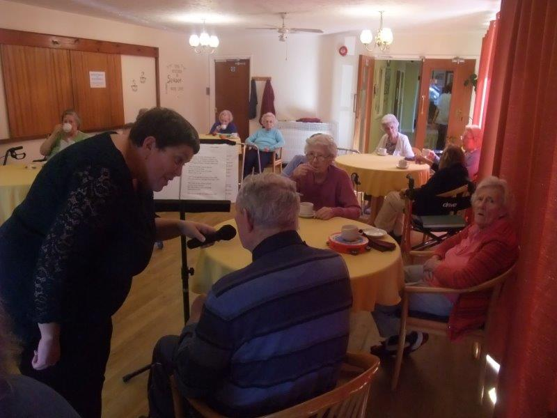 Resident Peter taking over the microphone at Dorrington House Dereham. Entertainer Carolyn encouraged all residents to have a go on the microphone but some preferred not to!