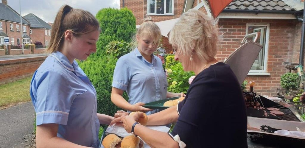 Carers Tyler and Becky grabbing some burgers and hot dogs for residents with Lorraine Dorrington at Dorrington House Watton's 20th Birthday!
